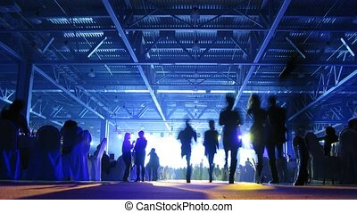 Different people silhouettes passing in front of bright lights