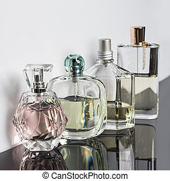 Different perfume bottles with reflections. Perfumery, cosmetics.