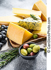 Different pieces of cheese with nuts olives and grapes. Assorted delicious snacks. Gray background. Top view