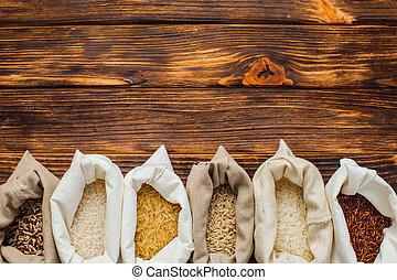 Different rice types in textile bags on wooden background