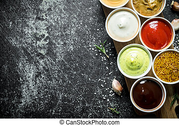 Different sauces in the bowls on the cutting Board.