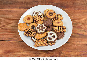 Different shortbread cookies on dish on rustic table