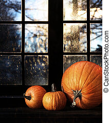 Different sized pumpkins in window for Halloween night