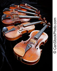 different sized violins on black velvet