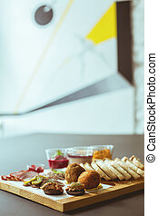 Different snacks on chopping board