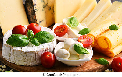 Different sorts of cheese on kitchen table.
