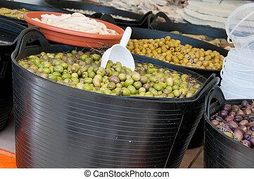 Different sorts of olives in big black barrels