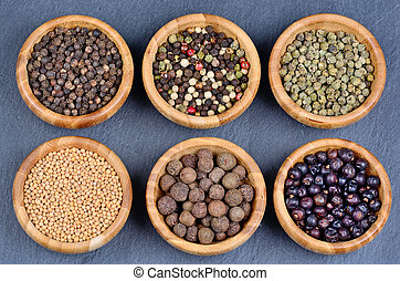 Different spices in a bowls on slate