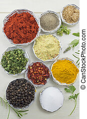 Different spices in shiny bowls on a white wooden table