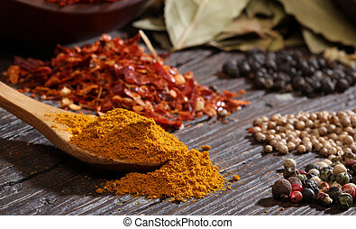 Different spices over a dark wood.