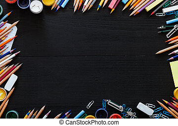 Different stationery supplies on dark table, creative educational background for website with color pencils, paints on black wooden desk, back to school concept, 1 september, top view, copy space