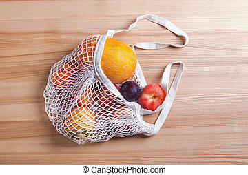 Different summer fruits in reusable shopping bag on the wooden table