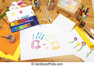 different things lying on a table to try arts and crafts, painted by kids