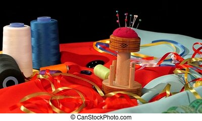 Different threads, needles, meter on bright blue and red clothes, black background, rotation