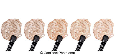 Different tones of foundation with makeup brush on white...