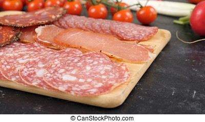 Different type of salami on wooden board. Dolly footage