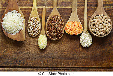 Different types of cereals in wooden spoons - buckwheat, chickpeas, rice, quinoa, lentils