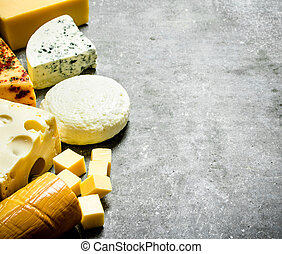 Different types of cheese. On stone table.