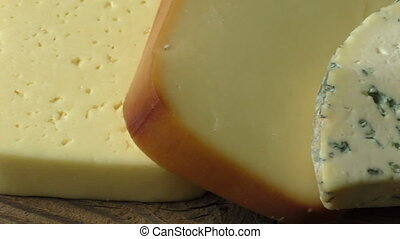 Different types of cheeses on wooden table