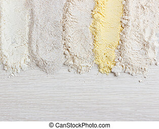 Different types of flour on wooden table