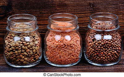 Different types of lentils in a jars on table