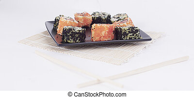 different types of Maki sushi on a black plate