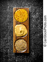 Different types of mustard in wooden stand.
