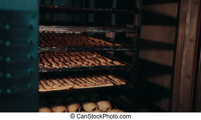 Shelvings with different types of pastry are moving inside hot bakehouse oven. Pastry is baked, lying on trays behind glass door, while turning of rack.