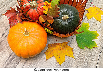 Different types of pumpkins and autumn leaves on a wooden table