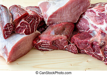 Different types of raw pork meat and beef. Raw meat on wooden table.