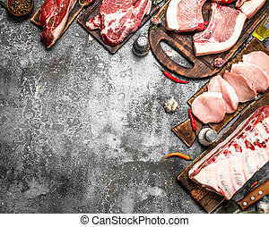Different types of raw pork meat and beef with spices and herbs.