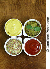 different types of sauces - ketchup, mustard, pesto