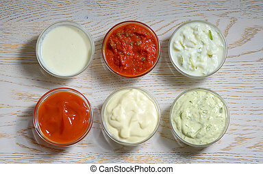 different types of sauces on wooden table