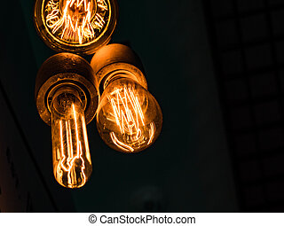 Different types of vintage glowing light bulbs on black. Edison lamps