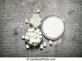 Different types of white sugar in a glass .