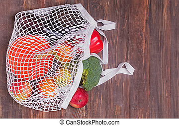 Different vegetables from farmer's market in reusable shopping bag on the wooden table