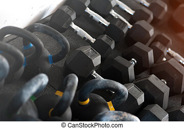 Different weights kettle bells and dumbbells on the floor
