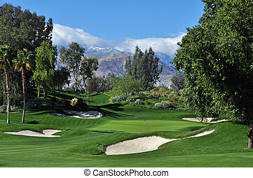 A well bunkered approach to a golf green with snow capped mountains in the background