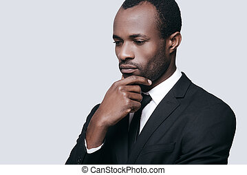 Difficult decision. Portrait of confident young African man holding hand on chin and looking away while standing against grey background