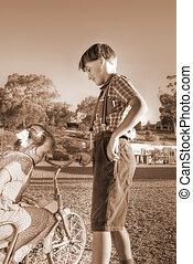 diffused image of a young gentleman helping a little girl of the old tricycle