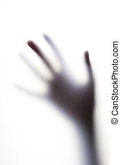 Diffused shadow of hand with thin fingers behind the frosted glass