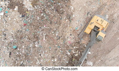 Drone shot of digger working, clearing and delivering rubbish piled on a landfill full of trash. Global environmental issue of waste disposal.