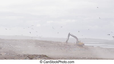 Flock of birds flying over digger working and clearing rubbish piled on a landfill full of trash with cloudy overcast sky in the background in slow motion