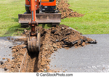 Digger machine operate for digging soil and repair road in the public park