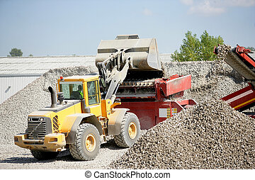 Digger moving gravel