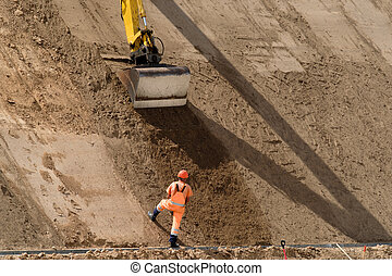 Digger works at new road construction site