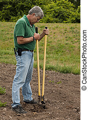 digging ahole - man preparing to erect a fence by digging a...