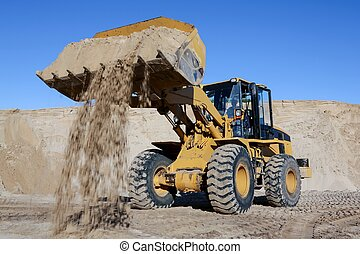 Digging and loading sand with a machine in a quarry