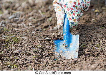 Digging the hole in the soil with a garden blade