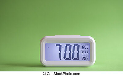 Digital alarm clock on table with green background.